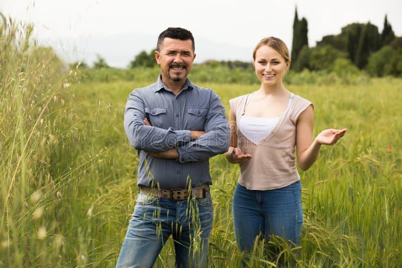 Hombre maduro y mujer que se colocan en campo de trigo fotos de archivo