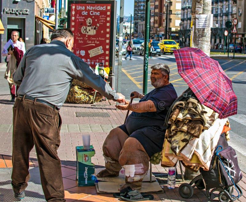 Hombre malsano pobre que pide limosnas en la calle de Murcia, España El hombre da el dinero a los pobres imagen de archivo