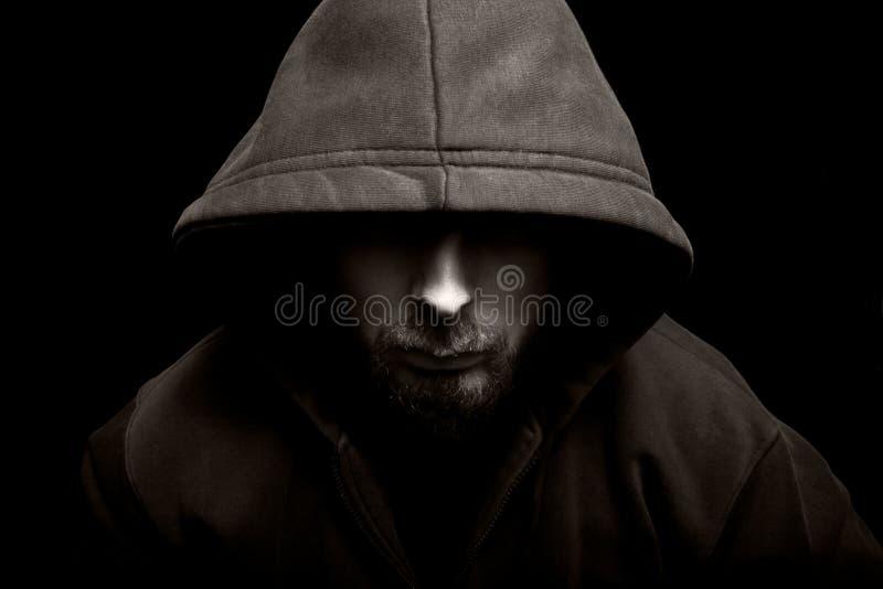 Hombre malvado asustadizo con el capo motor en la obscuridad imagen de archivo libre de regalías