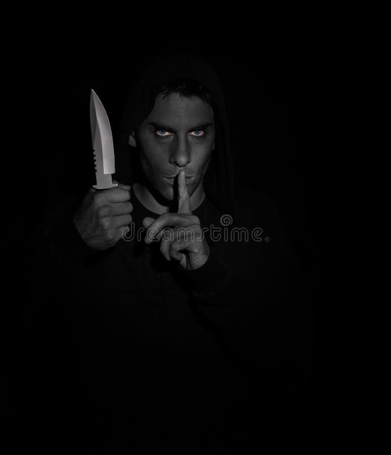 Hombre malvado que gesticula silencio mientras que sostiene un cuchillo fotos de archivo libres de regalías