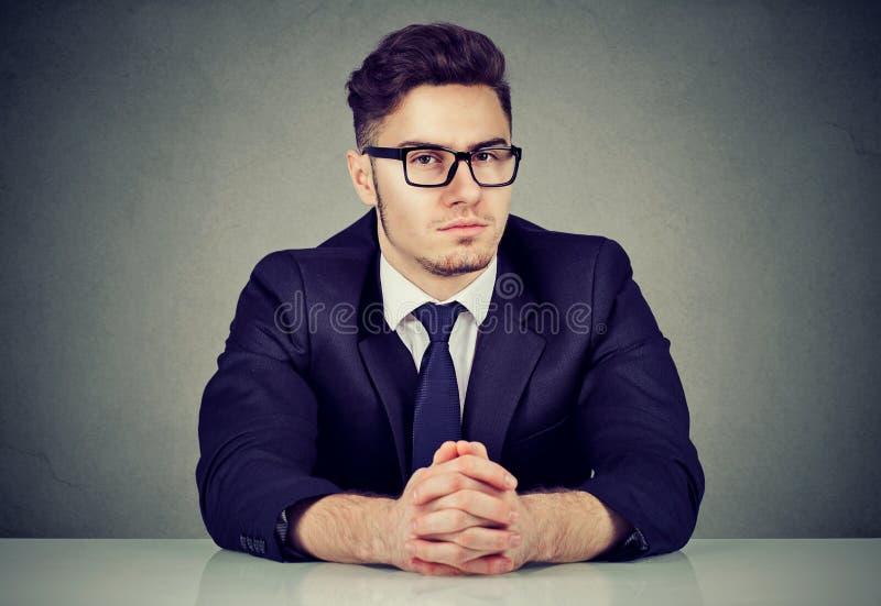 Hombre mandón confiado en la tabla fotografía de archivo
