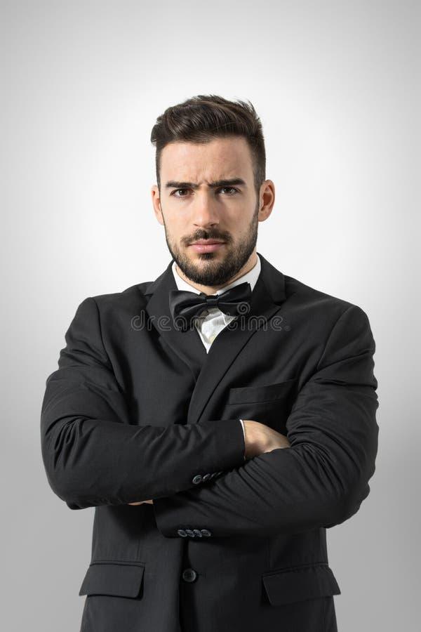 Hombre mandón enojado en smoking con la cámara de mirada intensa cruzada de los brazos en fotografía de archivo libre de regalías