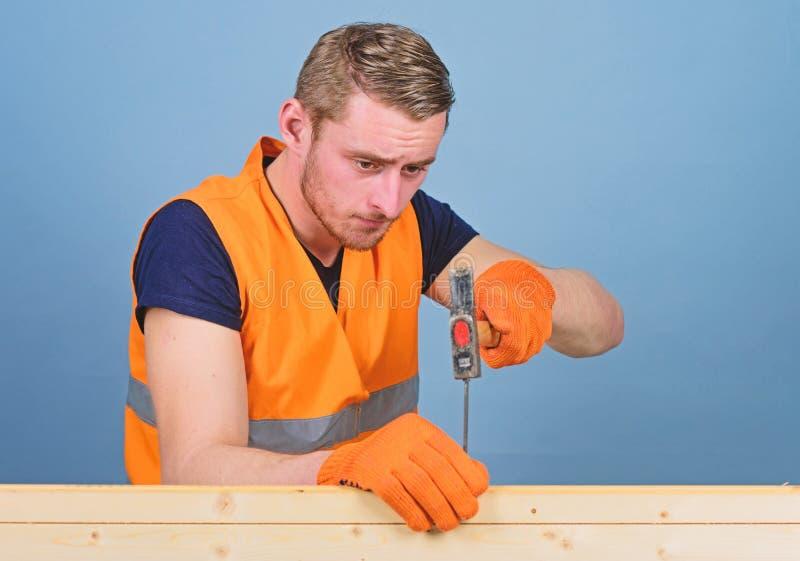Hombre, manitas en el trabajo de guantes uniformes y protectores handcrafting, fondo azul claro Carpintero, carpintero imágenes de archivo libres de regalías