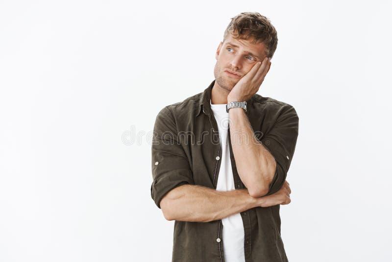 Hombre masculino europeo lindo cambiante triste y solo con la cabeza que se inclina de la barba y del pelo rubio en la palma de l foto de archivo libre de regalías