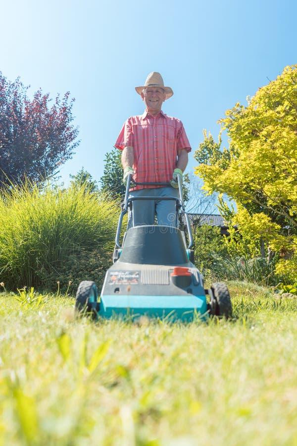 Hombre mayor activo que sonríe mientras que usa una cortadora de la hierba en el jardín fotografía de archivo libre de regalías