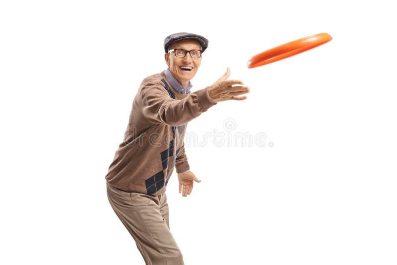 Hombre mayor alegre que juega con un disco volador fotografía de archivo