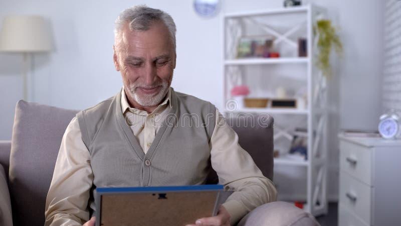 Hombre mayor alegre que mira la imagen y que sonríe, recordando momentos del placer imagen de archivo