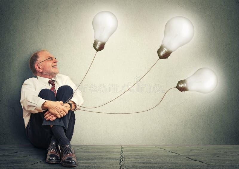 Hombre mayor alegre que sostiene tres bombillas teniendo muchas idea foto de archivo