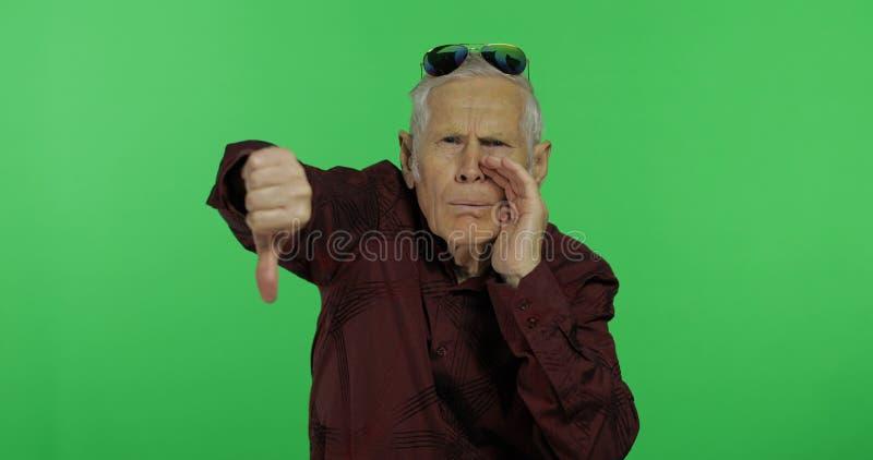 Hombre mayor algo que da el pulgar abajo Viejo hombre hermoso que muestra descontento imágenes de archivo libres de regalías