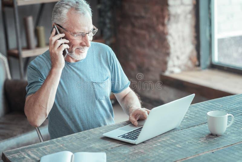 Hombre mayor amistoso que usa el ordenador portátil y teniendo conversación telefónica imagen de archivo libre de regalías