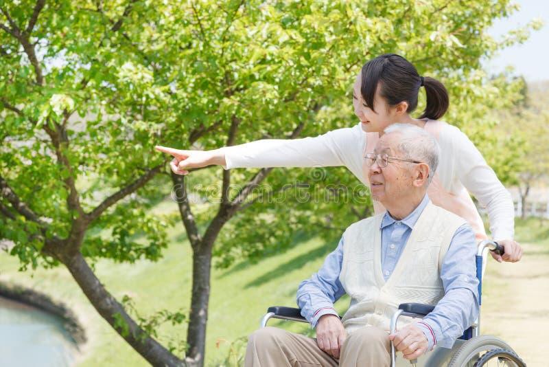 Hombre mayor asiático que se sienta en una silla de ruedas con señalar del cuidador fotos de archivo