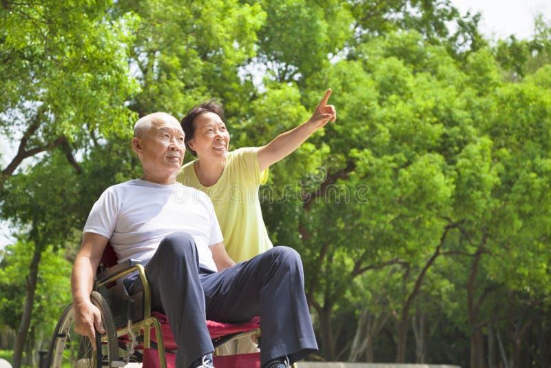 Hombre mayor asiático que se sienta en una silla de ruedas con su esposa imagen de archivo libre de regalías