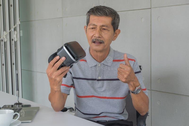 Hombre mayor asiático, sosteniendo los vidrios de VR con la sensación felices para la tecnología moderna imágenes de archivo libres de regalías