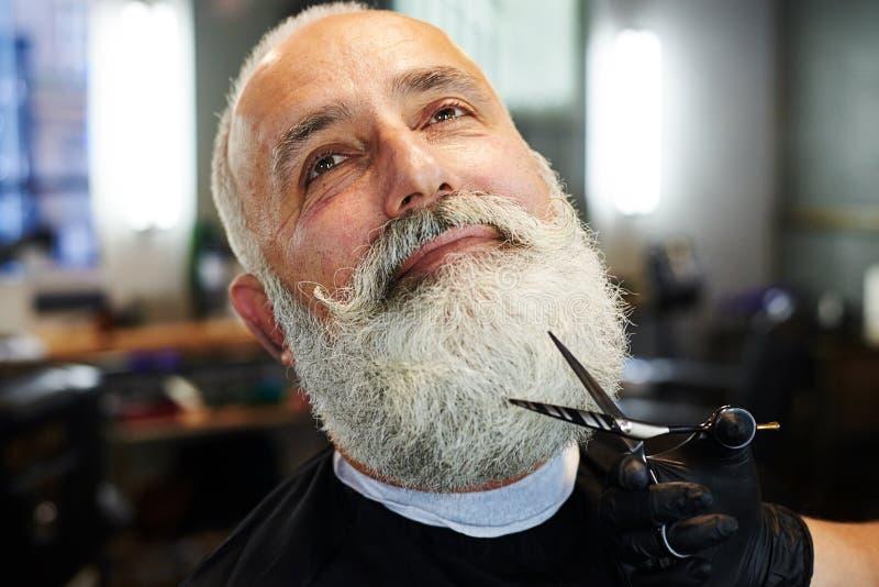 Hombre mayor barbudo en peluquería de caballeros imagen de archivo libre de regalías
