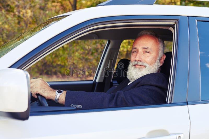 Hombre mayor barbudo hermoso en su coche fotos de archivo