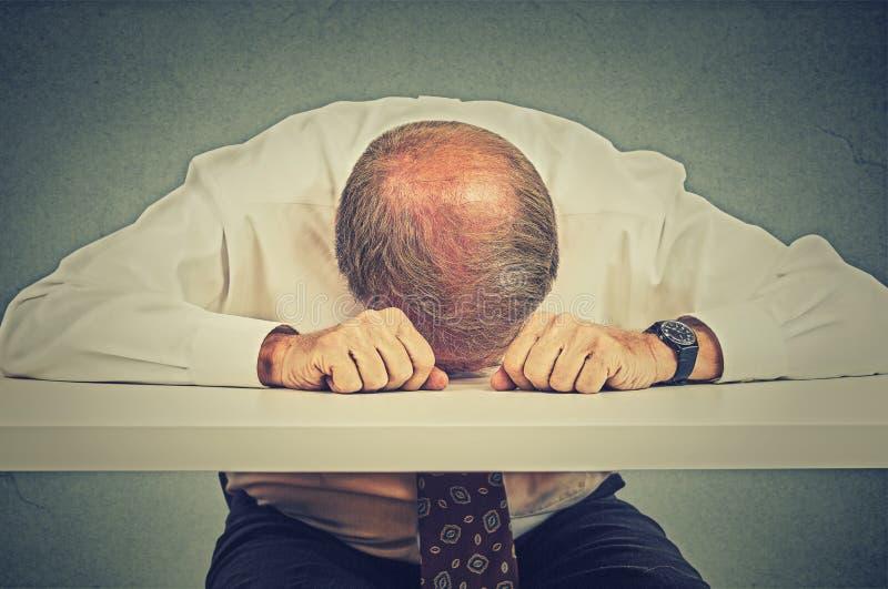 Hombre mayor cansado que duerme en su oficina fotografía de archivo
