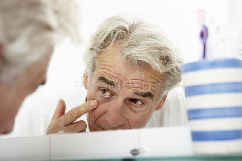 Hombre mayor cansado que mira la reflexión en espejo del cuarto de baño foto de archivo libre de regalías
