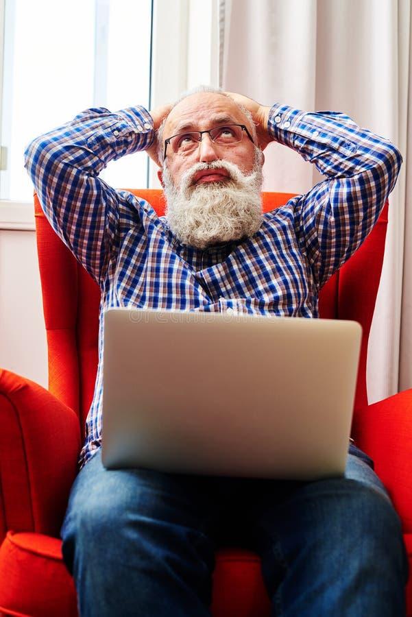 Hombre mayor cansado que se sienta en la silla con el ordenador portátil imágenes de archivo libres de regalías
