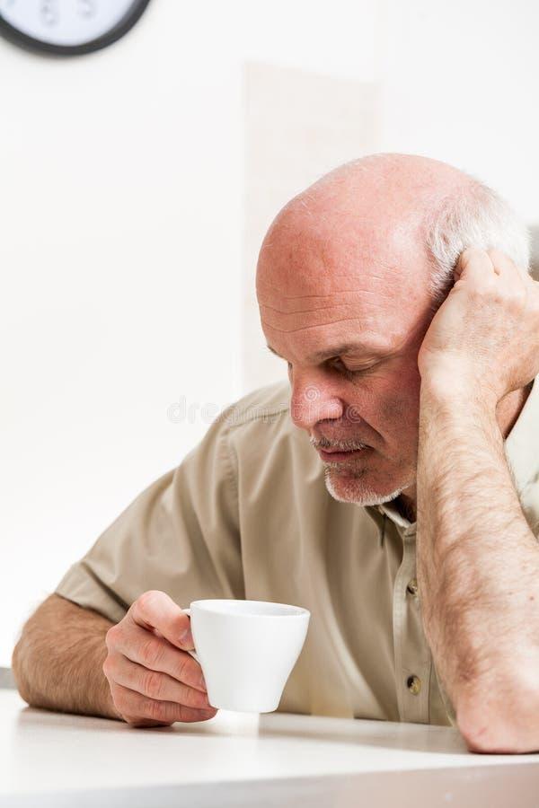 Hombre mayor cansado que se sienta en la tabla dentro imágenes de archivo libres de regalías