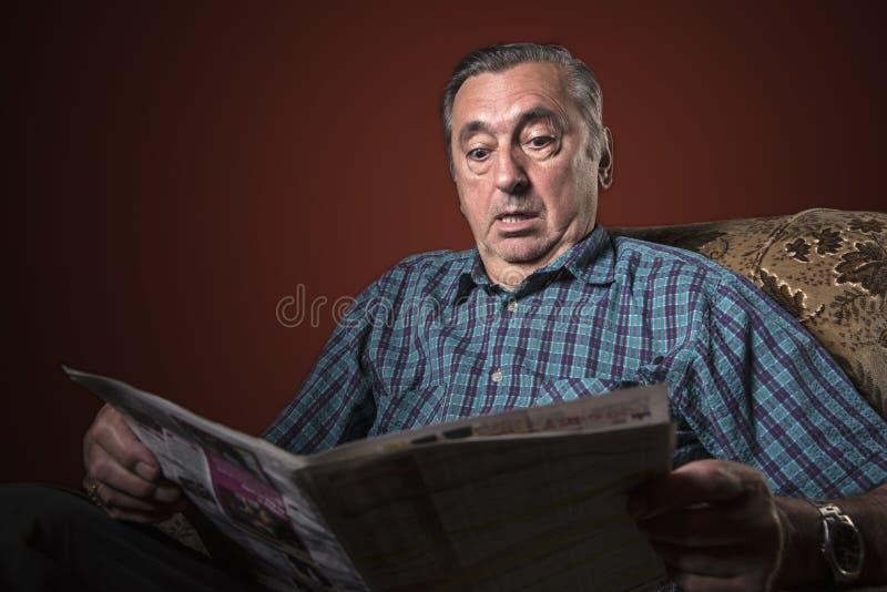 Hombre mayor chocado con noticias foto de archivo libre de regalías