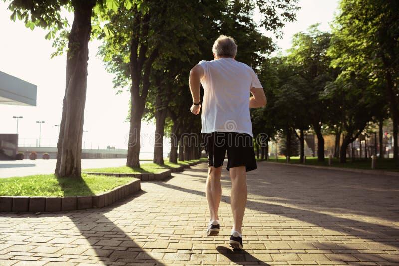 Hombre mayor como el corredor con el brazal o perseguidor de la aptitud en la calle de la ciudad fotos de archivo libres de regalías