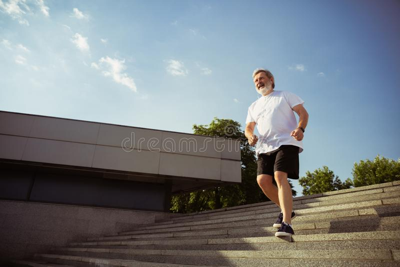 Hombre mayor como el corredor con el brazal o perseguidor de la aptitud en la calle de la ciudad foto de archivo