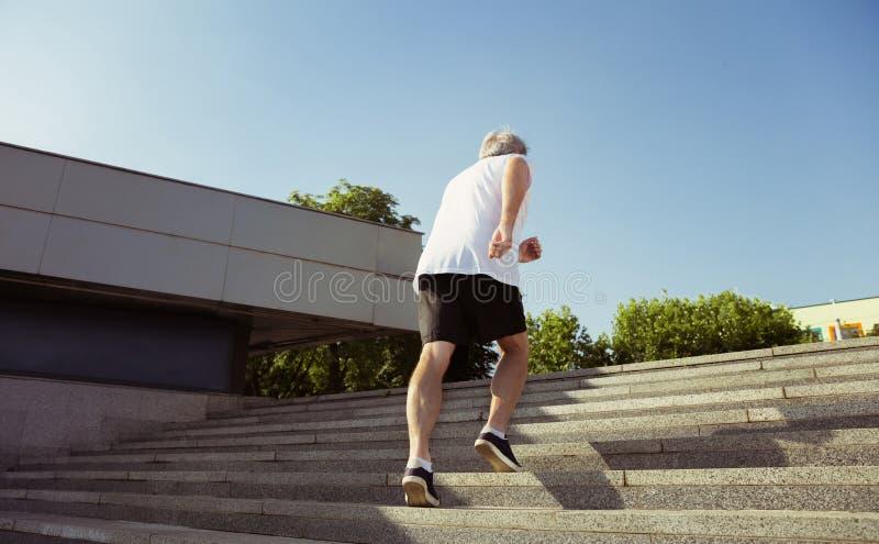 Hombre mayor como el corredor con el brazal o perseguidor de la aptitud en la calle de la ciudad imagen de archivo libre de regalías