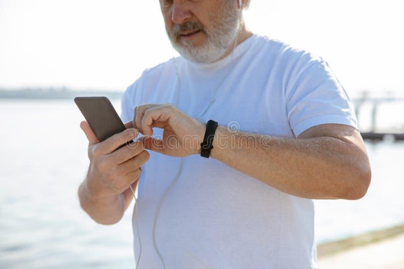 Hombre mayor como el corredor con el brazal o perseguidor de la aptitud en la orilla foto de archivo