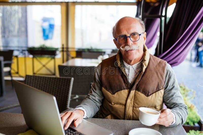 Hombre mayor con café de consumición del ordenador portátil en el café de la calle de la ciudad imagenes de archivo