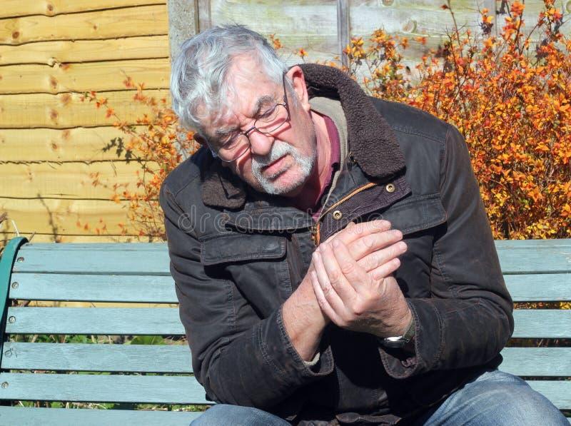 Hombre mayor con dolor de la mano. fotografía de archivo