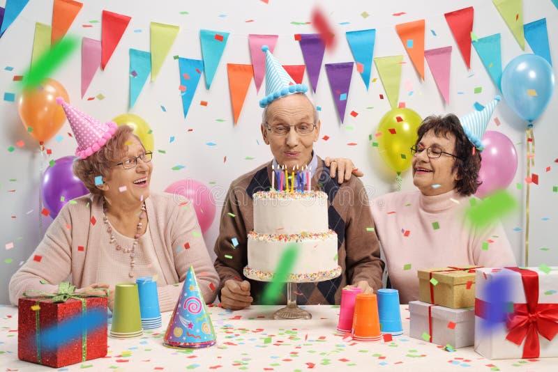 Hombre mayor con dos mujeres mayores que soplan velas en un cumpleaños fotografía de archivo libre de regalías