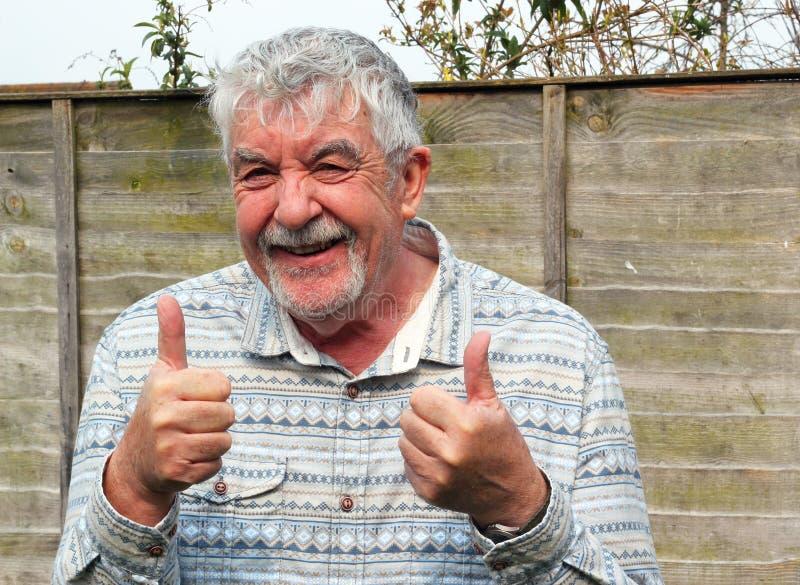 Hombre mayor con dos pulgares para arriba, muestra aceptable. imagen de archivo