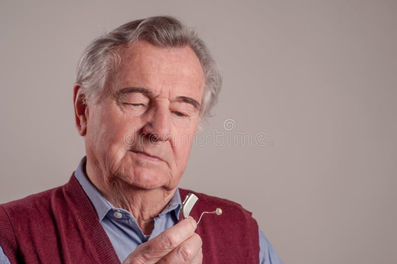 Hombre mayor con el audífono aislado imagen de archivo
