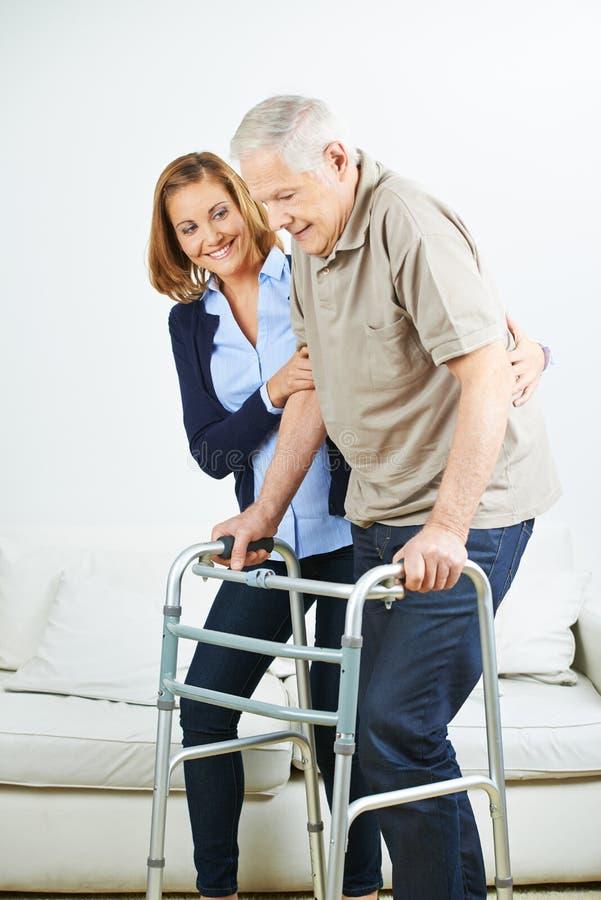 Hombre mayor con el caminante y el fisioterapeuta fotos de archivo