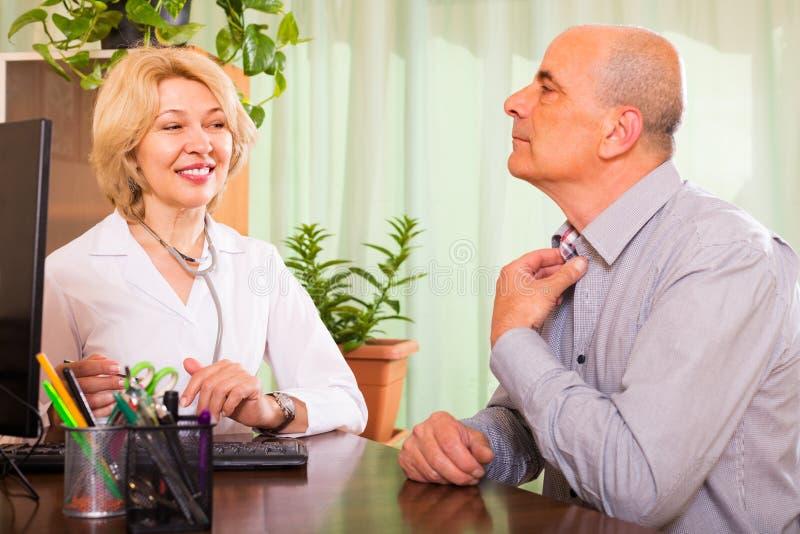 Hombre mayor con el doctor en clínica imagen de archivo libre de regalías