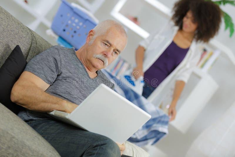 Hombre mayor con el ordenador portátil y planchar de la ayuda a domicilio fotografía de archivo libre de regalías