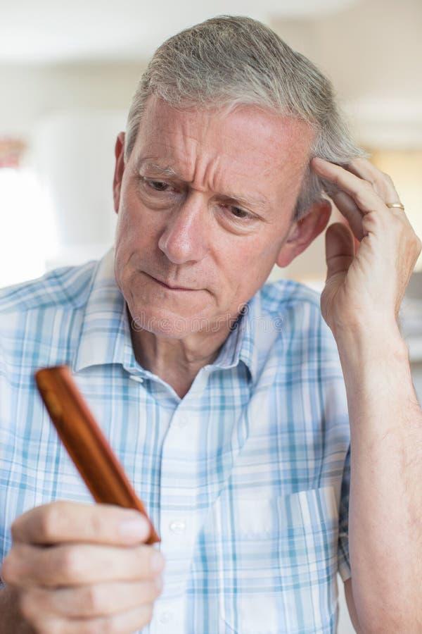 Hombre mayor con el peine referido sobre pérdida de pelo imagen de archivo