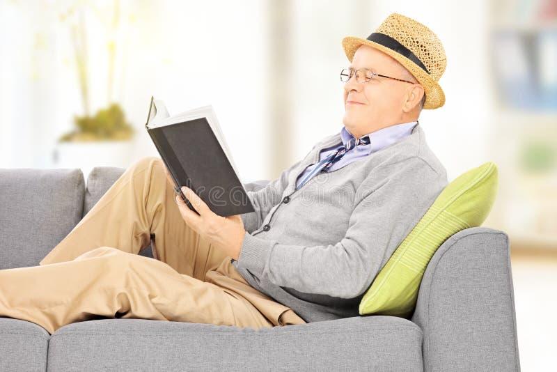 Hombre mayor con el sombrero en un sofá que lee una novela fotos de archivo