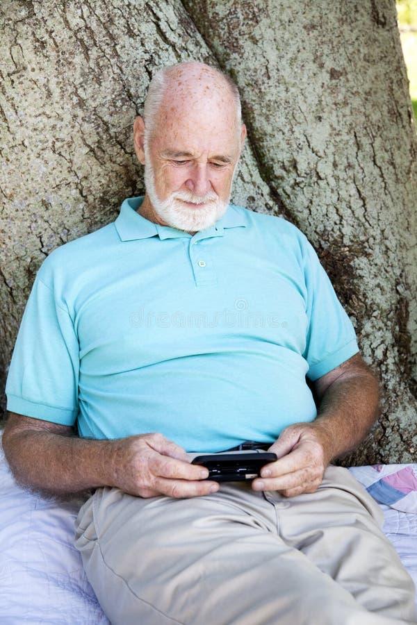 Hombre mayor con el teléfono elegante fotos de archivo libres de regalías