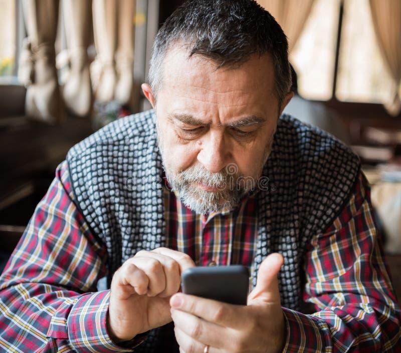 Hombre mayor con el teléfono elegante fotos de archivo