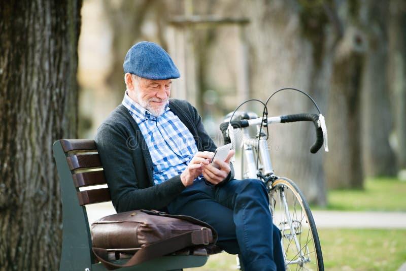 Hombre mayor con la bicicleta en ciudad, sosteniendo el teléfono elegante, mandando un SMS imágenes de archivo libres de regalías
