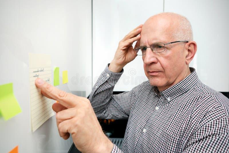 Hombre mayor con la demencia que mira notas imagen de archivo