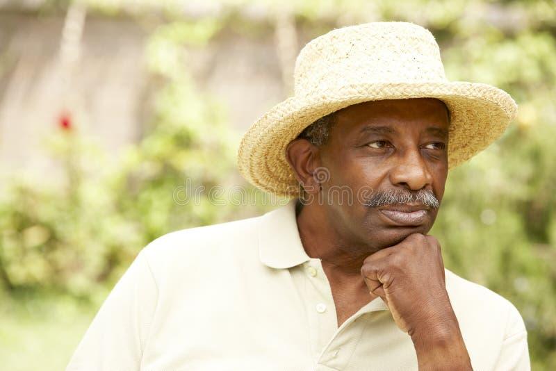 Hombre mayor con la expresión pensativa foto de archivo