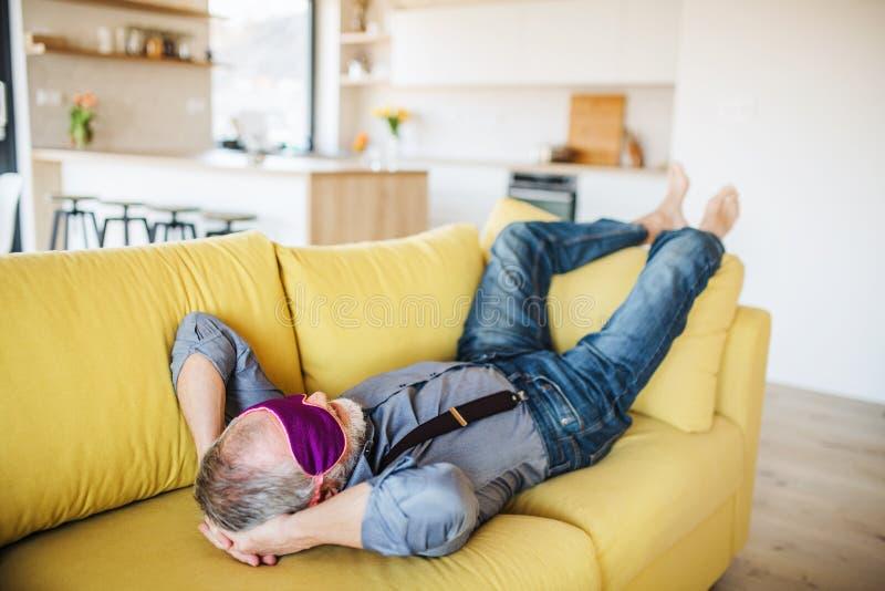 Hombre mayor con la máscara de ojo que miente en el sofá dentro en casa, relajándose foto de archivo libre de regalías