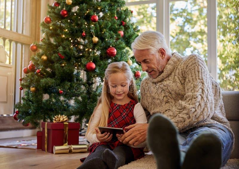 Hombre mayor con la nieta que usa la tableta digital durante Cristo imagen de archivo