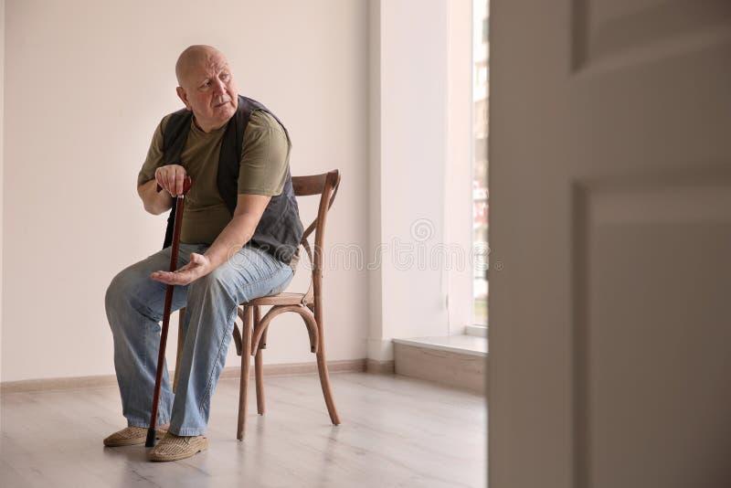 Hombre mayor con las monedas que se sientan en silla en sitio vacío fotos de archivo libres de regalías