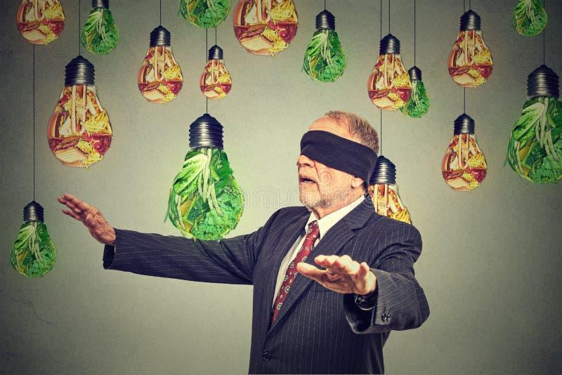 Hombre mayor con los ojos vendados que camina a través de las bombillas formadas como la comida basura y verduras verdes imagenes de archivo