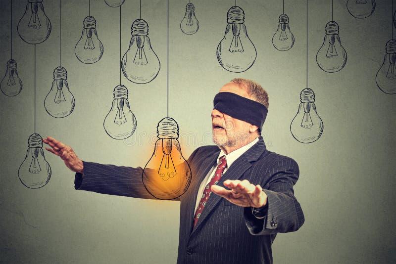 Hombre mayor con los ojos vendados que camina a través de las bombillas que buscan para la idea brillante fotografía de archivo