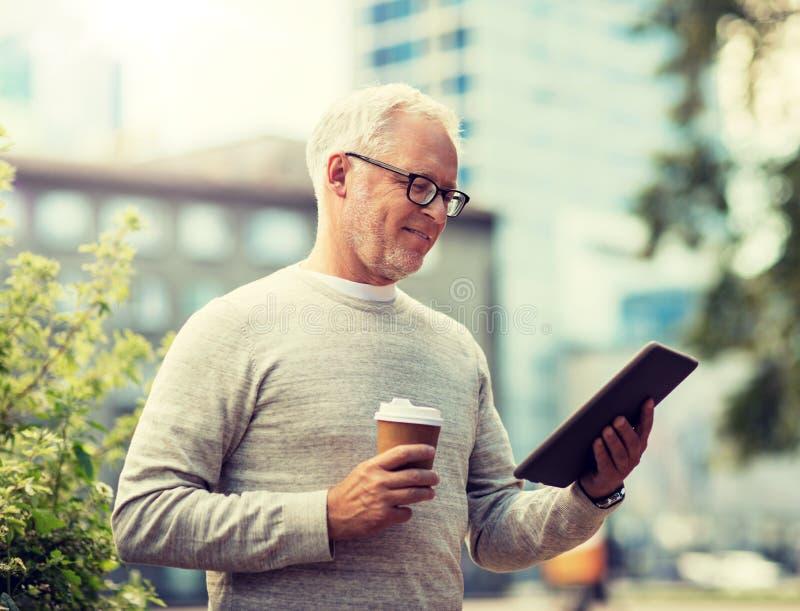 Hombre mayor con PC y caf? de la tableta en ciudad foto de archivo