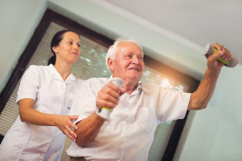 Hombre mayor con pesas de gimnasia en la rehabilitación con un fisioterapeuta imágenes de archivo libres de regalías